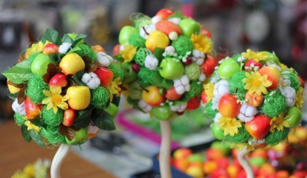 Создавая топиарий своими руками, можно использовать разнообразные украшения, ленты и цветы