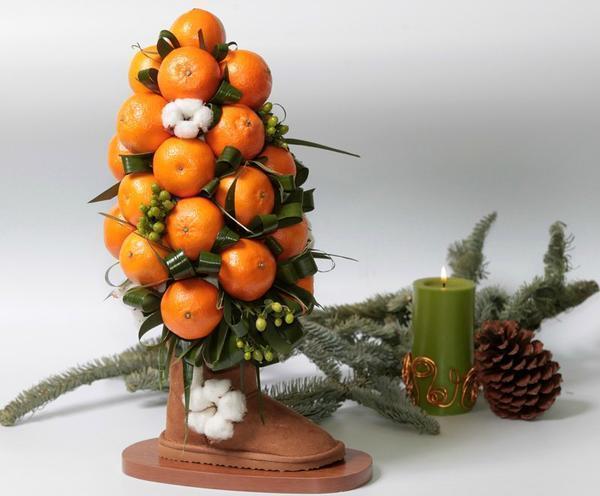 Мандарины давно стали одним из главных атрибутов новогодних праздников, поэтому топиарий с их использованием отлично украсит Вашу квартиру