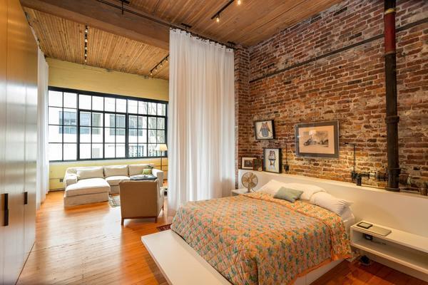 Брутальность стиля лофт отлично подойдет для гостиной, совмещенной со спальней